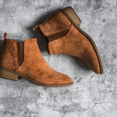 Classic suede brown women's chelsea boots on a gray background, top view